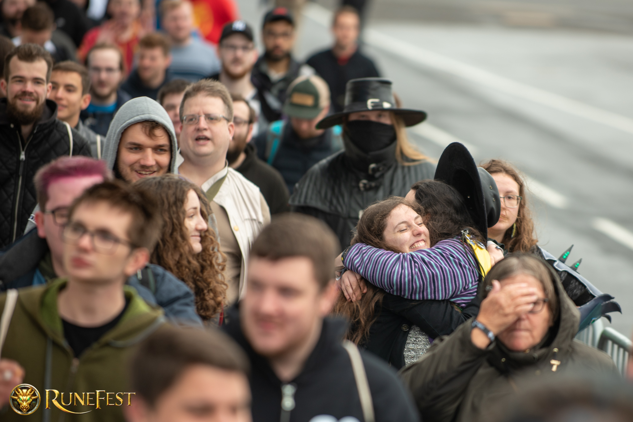 Runefest image - Two people hugging in the queue